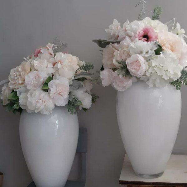 Bijele staklene vaze sa umjetnim bozurima